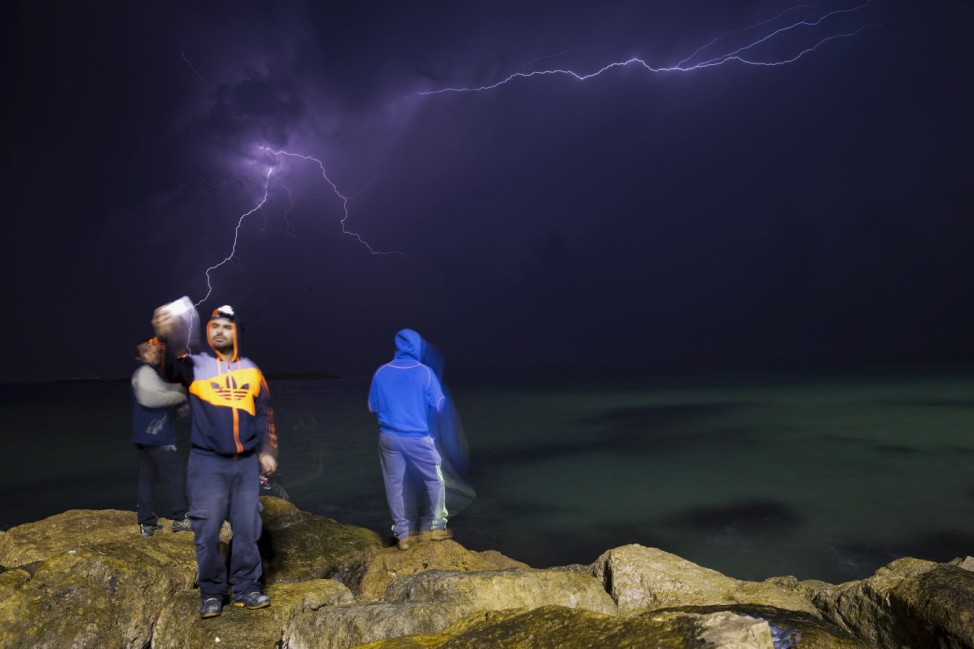 Fishermen stand on rocks in front of the sea as a lightning storm approaches, in the southern city of Ashkelon