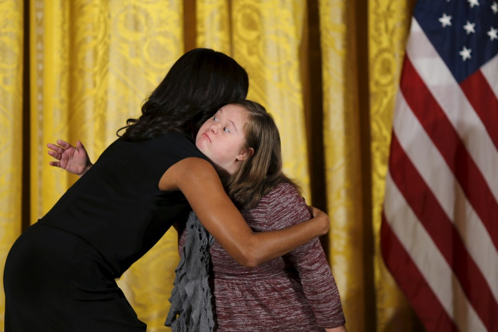 Meghan McNeal embraces first lady Michelle Obama as she receives the 2015 Urban Artisans Awards during the National Arts and Humanities Youth Program Awards ceremony at the White House in Washington