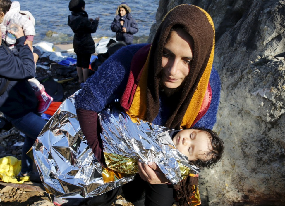 An Afghan migrant carries her baby after arriving by a raft on the Greek island of Lesbos