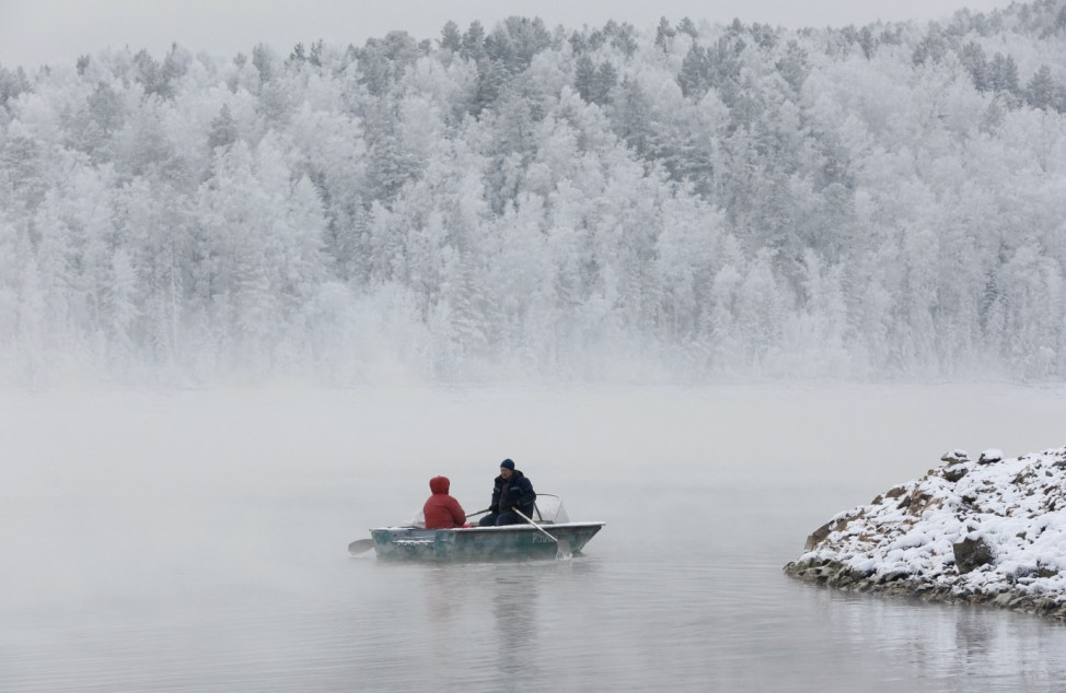 A man and a woman travel in a rowboat along the Yenisei River through a frosty fog in the Taiga district, outside the Siberian city of Krasnoyarsk, Russia