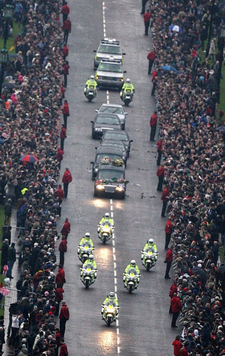 Thousands watch the funeral cortege of George Best arriving covered in flowers at Stormont in Belfast