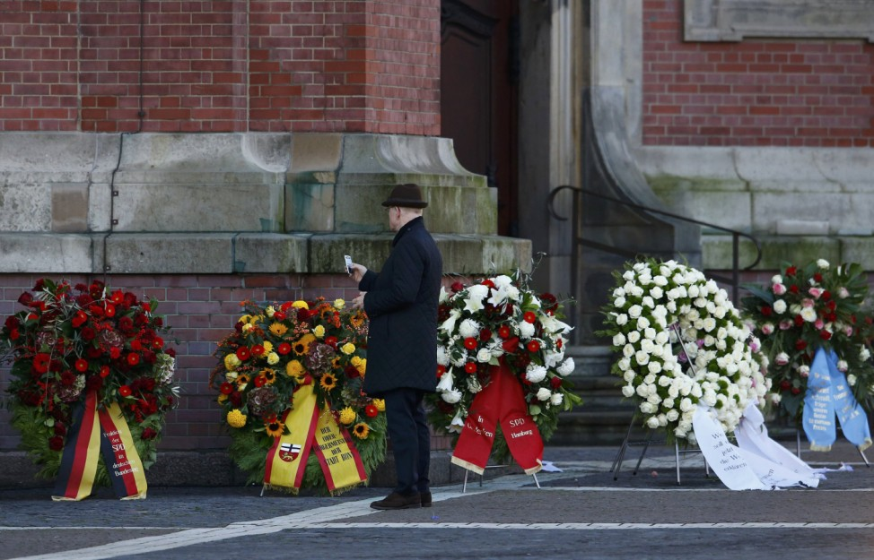 A man takes a picture of the wreaths placed outside the St. Michael's Church in Hamburg