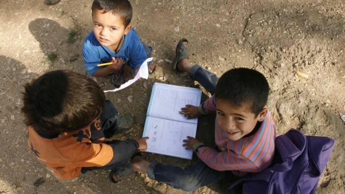 Syrische Kinder lesen in einem Flüchtlingslager im Libanon ein Schulbuch