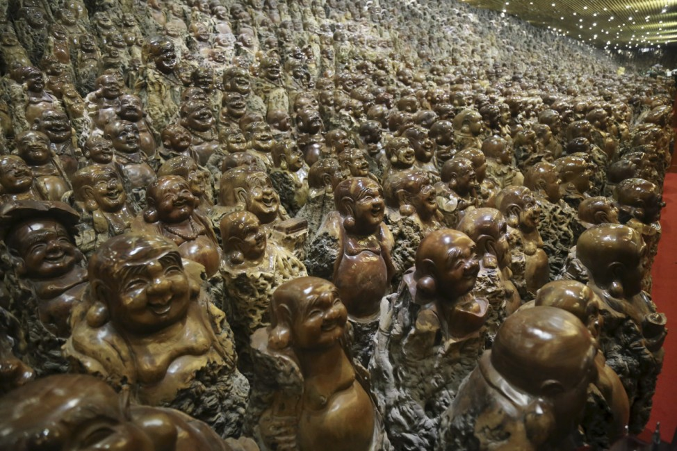 Buddha sculptures made of trunks of Chinese date trees are seen inside a room of a company selling dates, in Zhengzhou