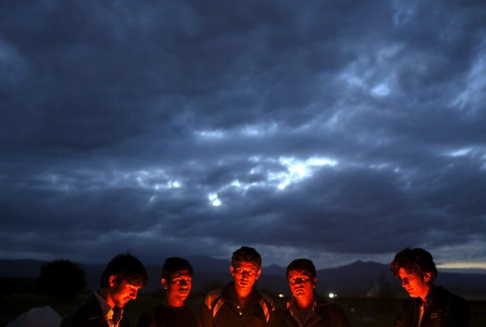 Pakistani migrants keep warm at the Greek-Macedonian border