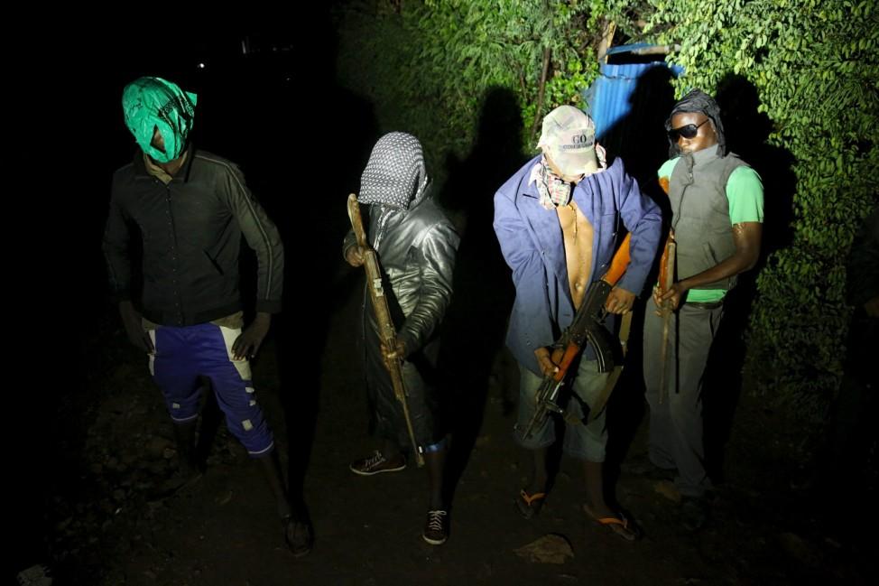 Armed vigilantes hold guns before a patrol in the center of Bujumbura, Burundi