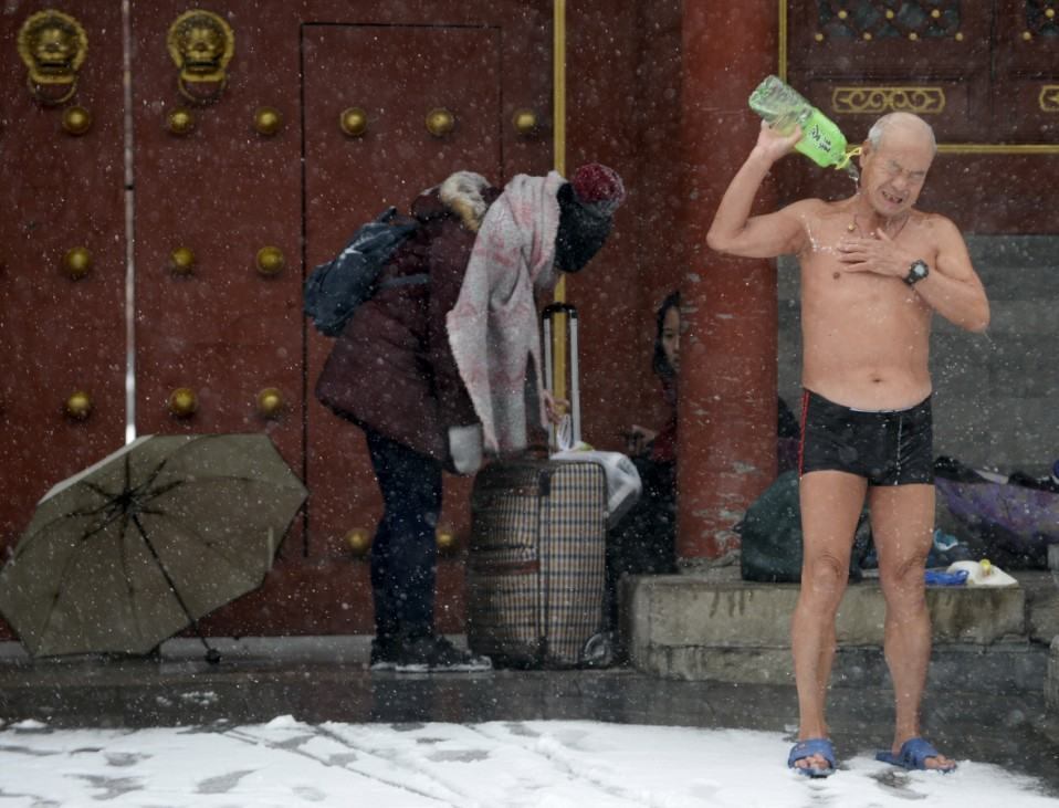 A winter swimmer pours water on his body to clean up after swimming in the Shichahai Lake amid heavy snowfall in Beijing