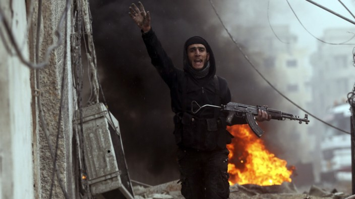 A Free Syrian Army fighter gestures in front of a burning barricade during heavy fighting in the Ain Tarma neighbourhood of Damascus