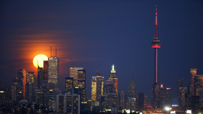 The moon rises behind the Canadian landmark CN Tower, and the skyline of Toronto