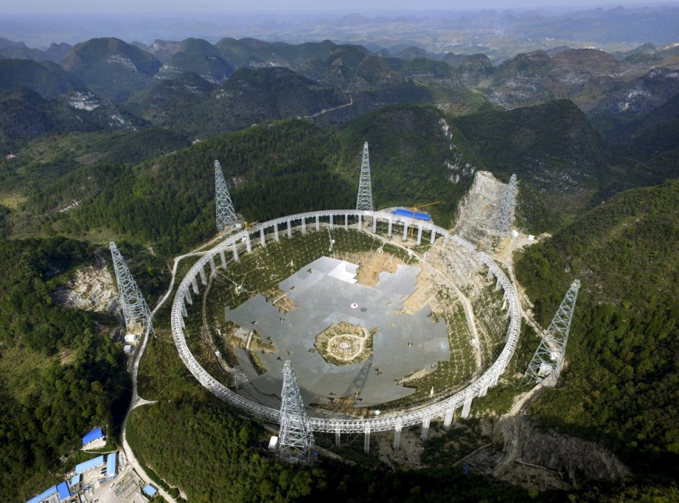 A 500-metre (1,640-ft.) aperture spherical telescope (FAST) is seen under construction among the mountains in Pingtang county