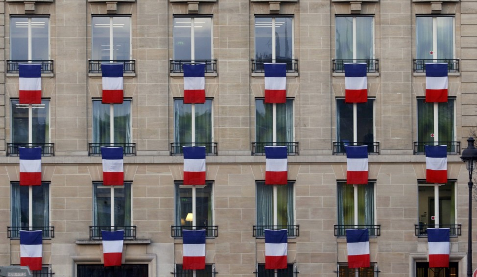 French flags hang from windows of a building near the Invalides in Paris to pay tribute to the victims of the Paris attacks