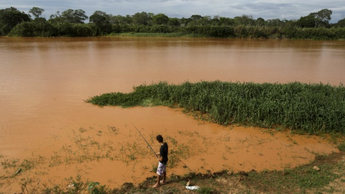 A resident fishes at Rio Doce, flooded with mud after a dam, owned by Vale SA and BHP Billiton Ltd burst, in Linhares