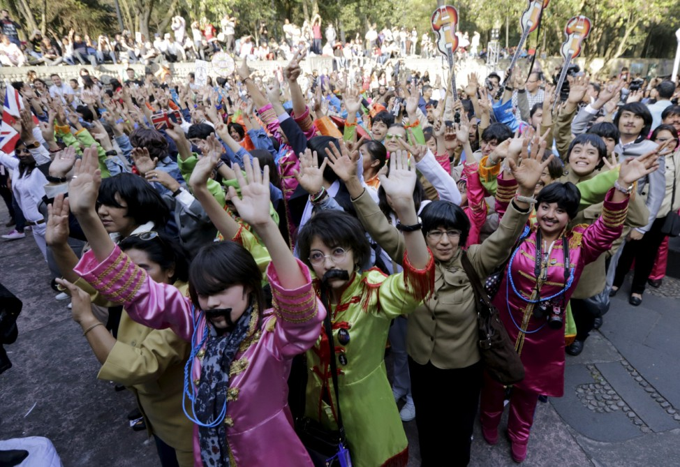 People wave as they take part in an attempt to set a Guinness World Record for the largest number of people dressed as members of the British band The Beatles at a park in Mexico City, Mexico