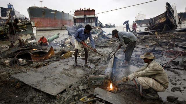 Workers weld a wrecked part of a ship at a ship-breaking yard in Chittagong.
