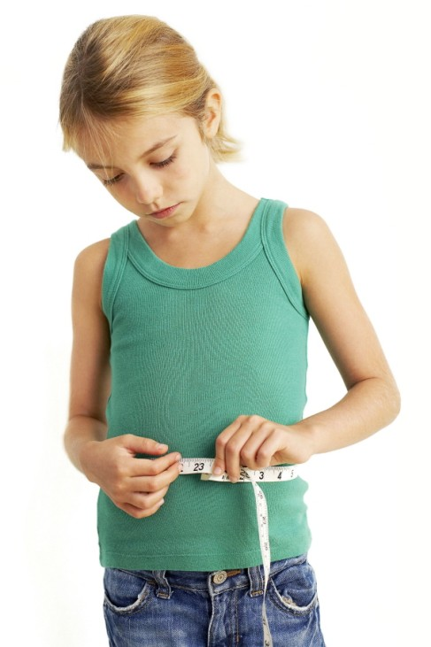Childhood dieting MODEL RELEASED Childhood dieting Eight year old girl measuring her waist with a