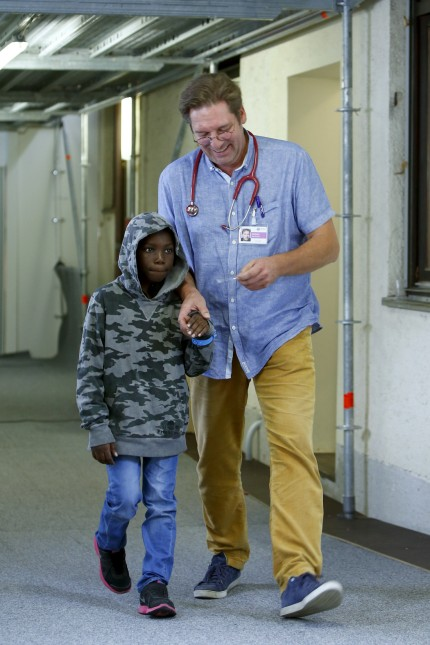 Migrant Kuapana from Congo arrives for a medical check-up with doctor Wendeborn, at a refugee camp set-up in the former German army base 'Bayernkaserne' in Munich