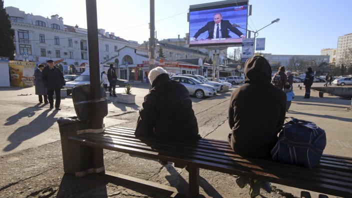A screen, showing Putin's annual end-of-year news conference, is on display in Sevastopol