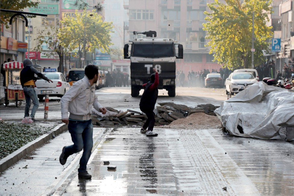 A demonstrator throws stones at a police vehicle during a protest against the curfew in Sur district