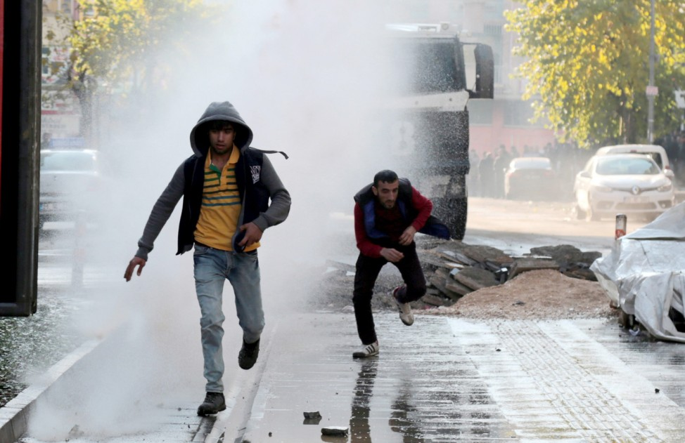 Riot police use a water cannon to disperse demonstrators during a protest against the curfew in Sur district
