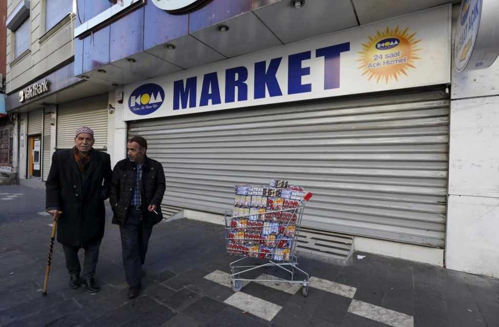 Men walk past a closed supermarket in Sur district which is partially under curfew, in the southeastern city of Diyarbakir, Turkey