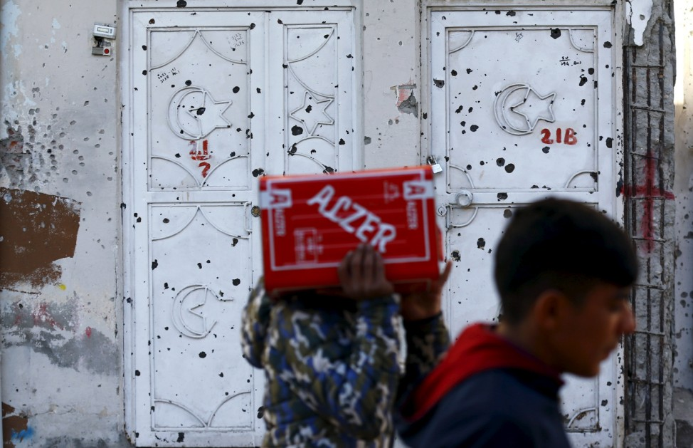 Men walk past a bullet-riddled house in the southeastern town of Silvan in Diyarbakir province, Turkey