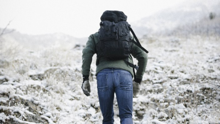 A man hiking through the mountains carrying a rucksack A man hiking through the mountains carrying