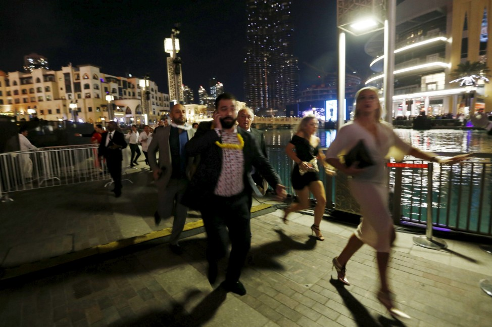 People run away as a fire engulfs the nearby The Address Hotel in downtown Dubai in the United Arab Emirates