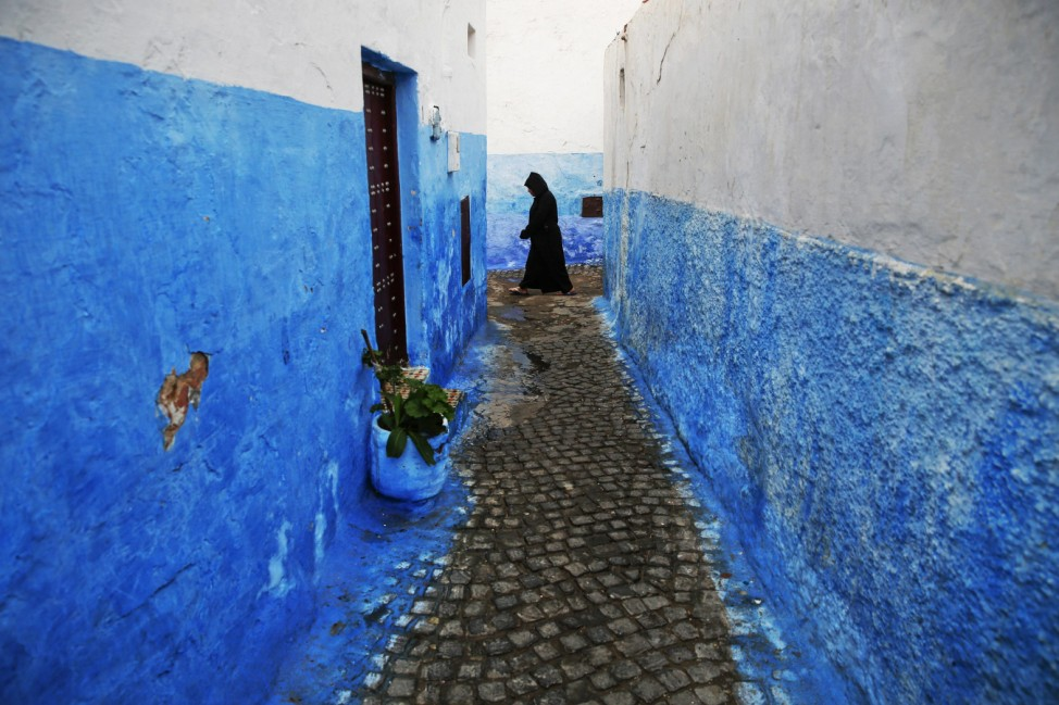 A woman makes her way between houses painted in traditional blue and white colours in Kasbah of the Udayas, a picturesque ancient part of Rabat
