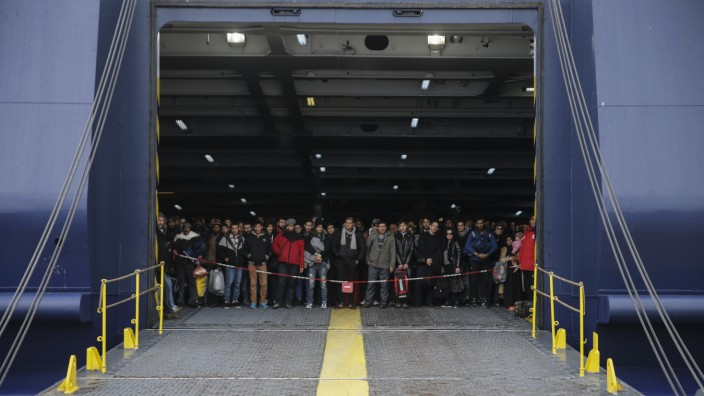 Refugees and migrants arrive aboard the passenger ferry Ariadne at the port of Piraeus, near Athens