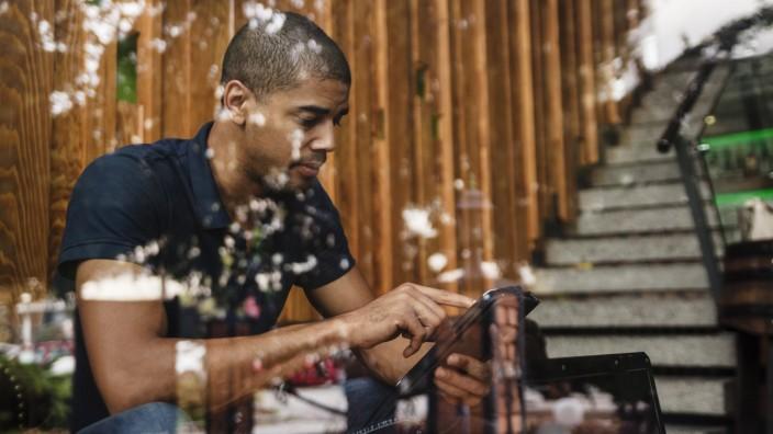 Man using digital tablet behind windowpane PUBLICATIONxINxGERxSUIxAUTxHUNxONLY ZEDF000002