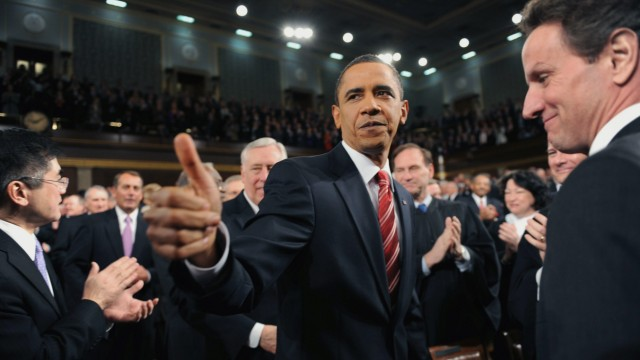 U.S. President Barack Obama walks down the center aisle greeting members of Congress on his way to deliver his first State of the Union address on Capitol Hill in Washington