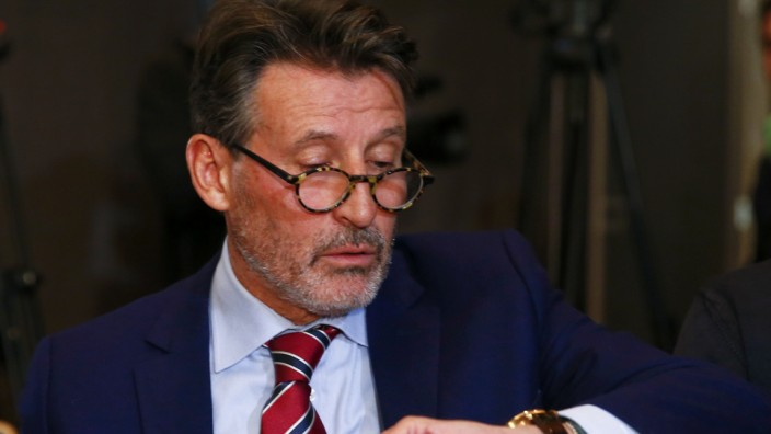 Coe, IAAF's President, checks time ahead of a news conference by WADA former president, Pound, who heads the commission into corruption and doping in athletics, in Unterschleissheim