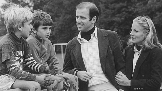 Joe Biden und seine zweite Frau Jill unterhalten sich mit Bidens Söhnen Hunter und Beau, die auf einer Mauer sitzen und im Grundschulalter sind.