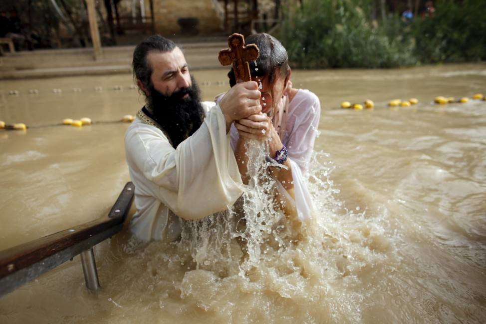 A Christian pilgrim is baptised as she takes part in a ceremony at the baptismal site known as Qasr el-Yahud on the banks of the Jordan River near the West Bank city of Jericho