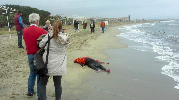 People take pictures as the body of a migrant lies on the shore in the Aegean coastal town of Ayvalik, Turkey