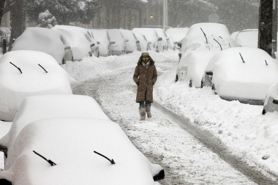 Eine Frau läuft über eine schneebedeckte Straße in Philadelphia.