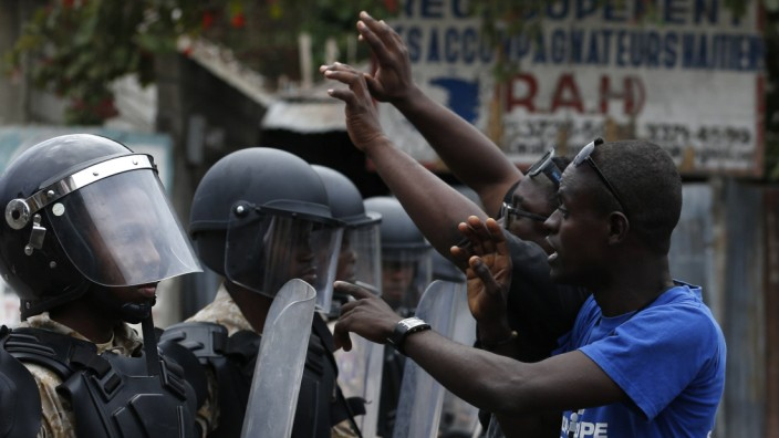 National Police agents watch demonstrators during a protest in order to ask for president Michel Mar