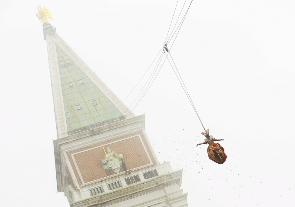 The traditional Columbine descends from Saint Mark's tower bell on an iron cable during the Venice Carnival