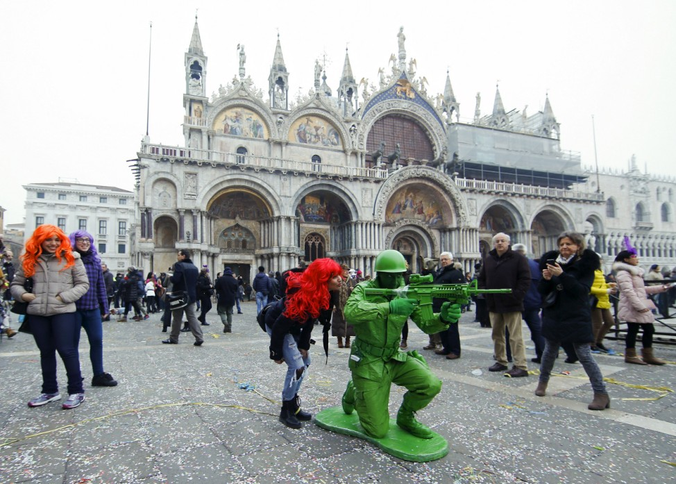A masked reveller poses at San Marco Piazza during the Venice Carnival