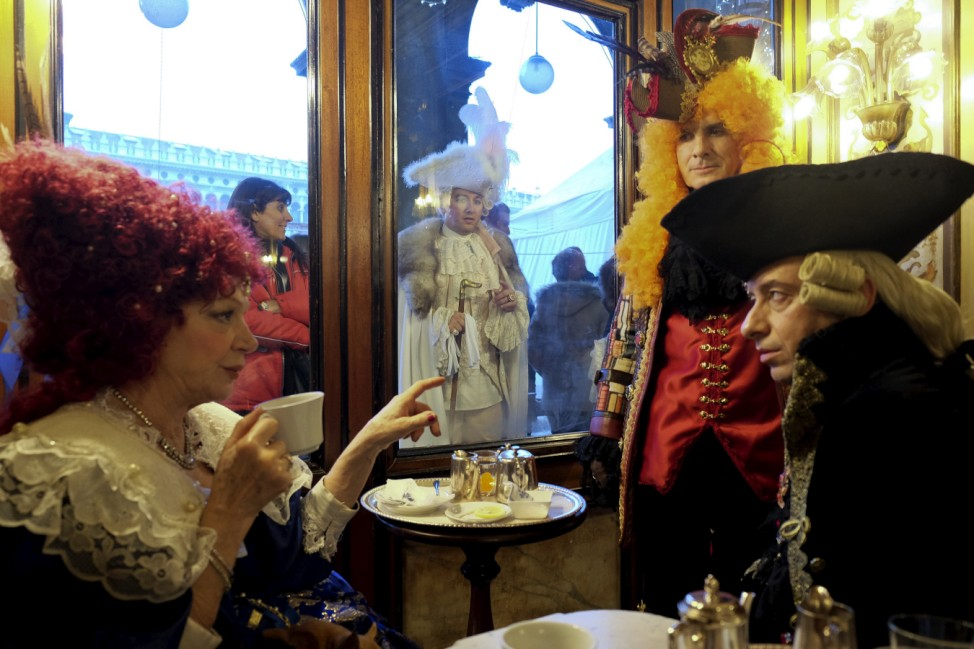 Revellers sit at the Caffe Florian coffee shop in Saint Mark's Square during the Venice Carnival, Italy