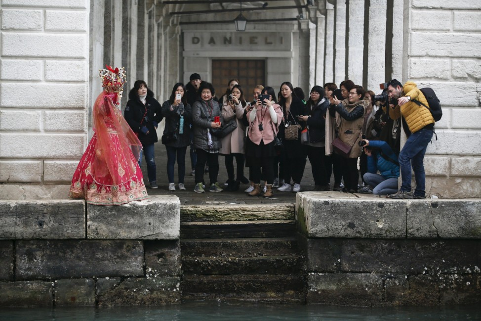 A masked reveller is pictured by tourists during the Venice Carnival, in San Marco Piazza