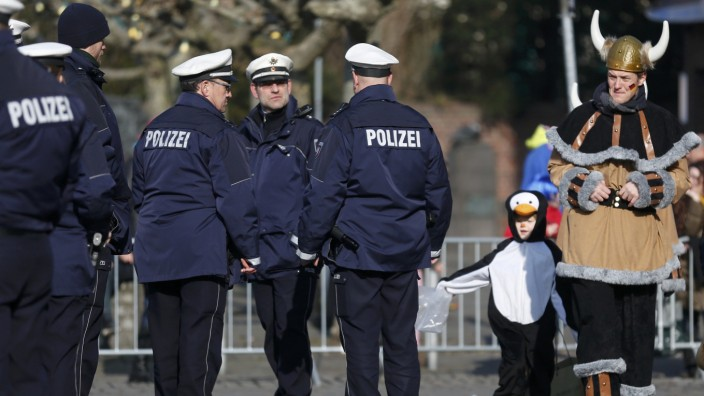 Carnival revellers walk past police during Rose Monday carnival parade in Duesseldorf