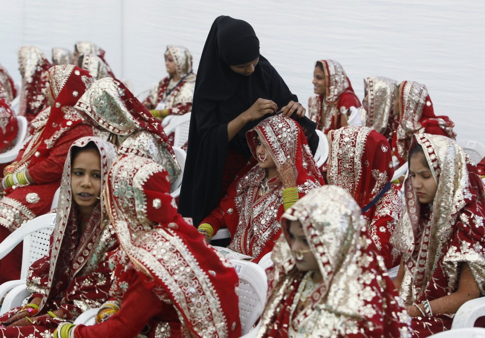 A Muslim bride is helped with her wedding dress, before the start of a mass marriage ceremony in Ahmedabad