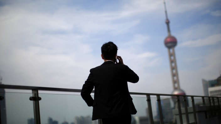 Man talks on a mobile phone near the Pudong financial district in Shanghai