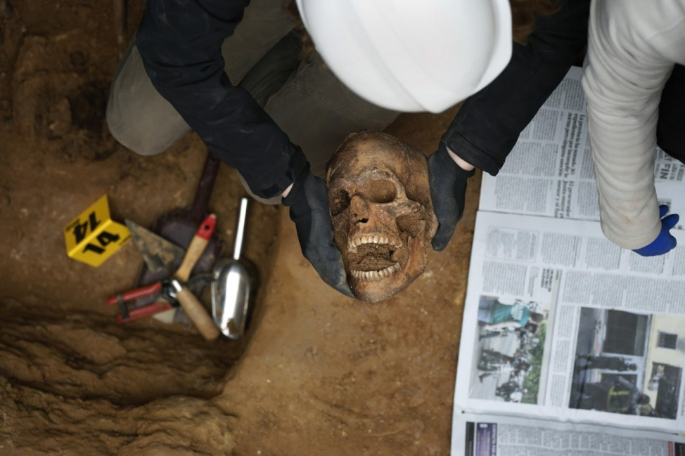 A member of the Association for the Recovery of Historical Memory (ARHM) holds a human skull during the exhumation of the grave in Guadalajara's cemetery