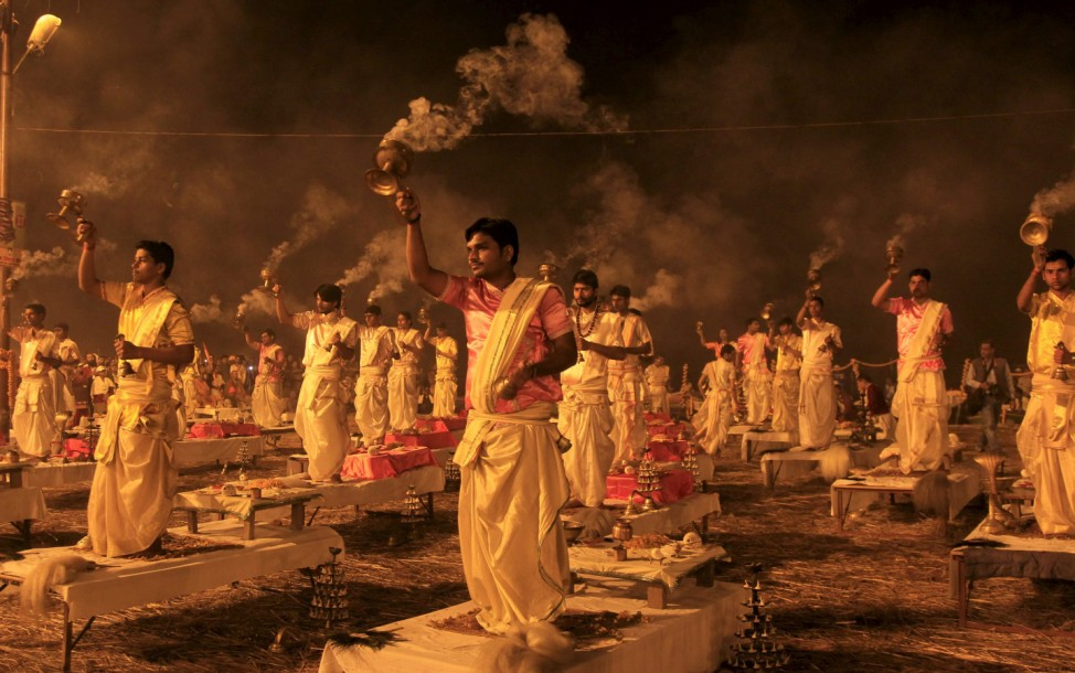 Hindu priests hold traditional incense lamps as they perform a ritual known as 'Aarti' on the banks of Sangam in Allahabad