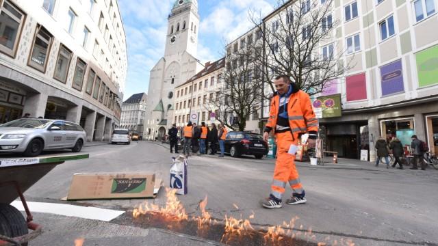 Fußgängerzone: Arbeiter pinseln eine weiße Sperrlinie auf die Straße.