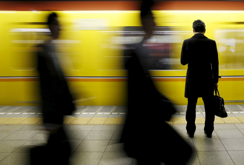 A man looks at his mobile phone as he waits for a subway at a station in Tokyo