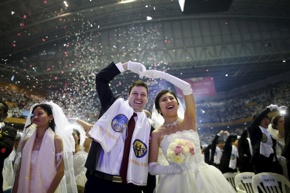 A newlywed couple celebrates during a mass wedding ceremony of the Unification Church at Cheongshim Peace World Centre in Gapyeong