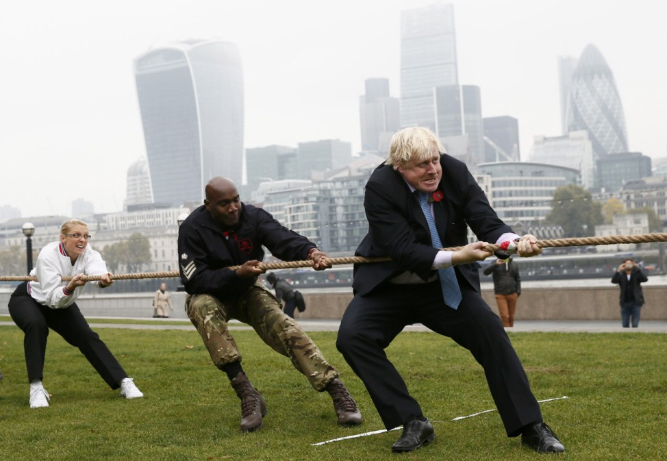 London Mayor Boris Johnson takes part in a tug of war with members of the armed services to launch the London Poppy Day, outside City Hall, in London